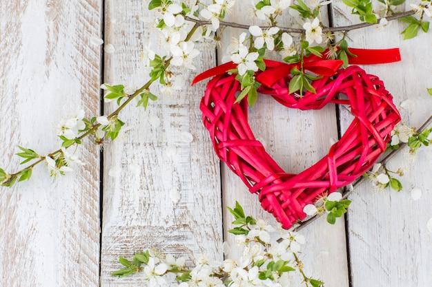 Un coeur en osier rouge et des branches de cerisier en fleurs Photo Premium