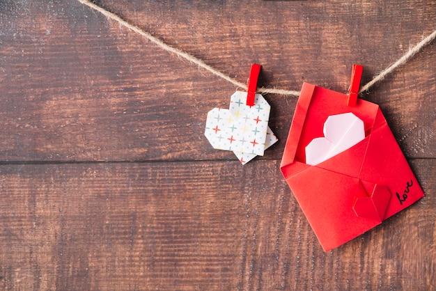 Cœur en papier et enveloppe avec des épingles qui s'emboîtent Photo gratuit