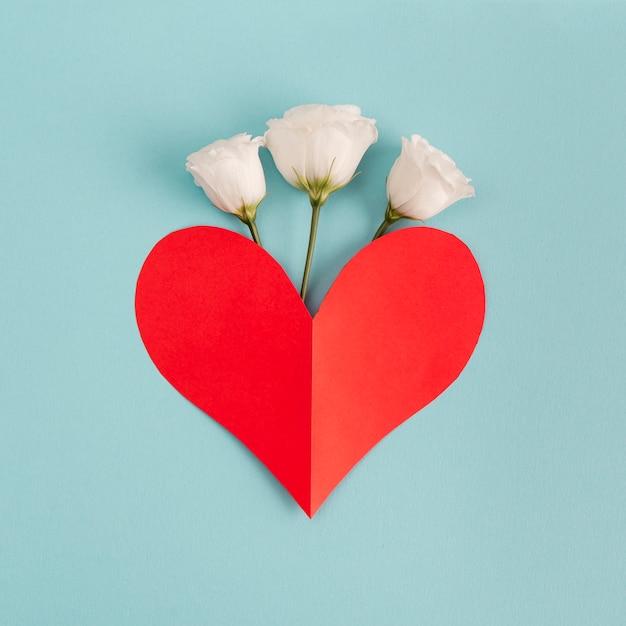 Coeur de papier rouge près de fleurs fraîches Photo gratuit