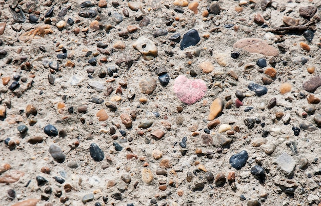 Coeur de pierre entre fond multicolore de pierres naturelles Photo Premium