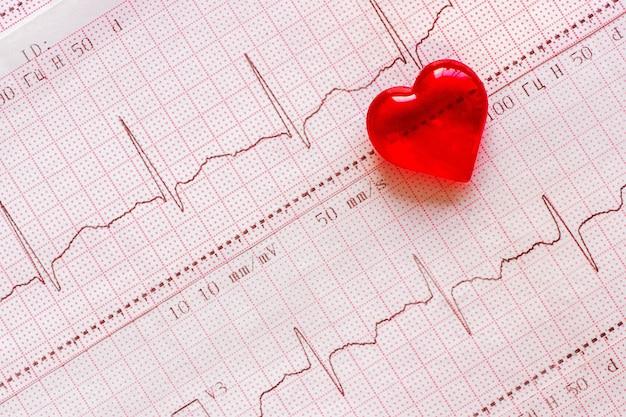 Cœur en plastique sur le fond de l'électrocardiogramme (ecg). journée du coeur en santé Photo Premium