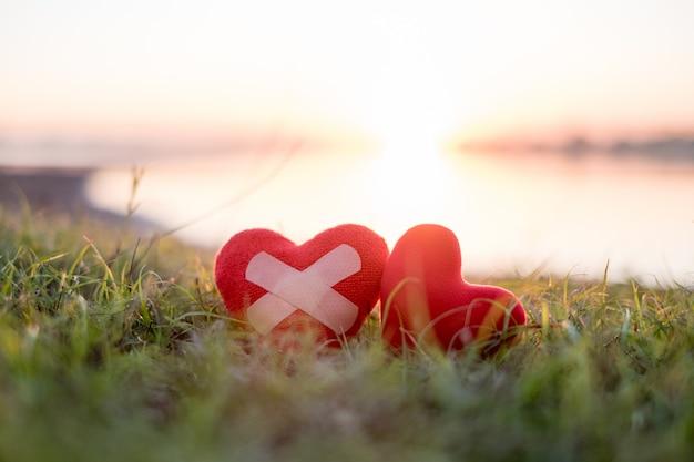 Coeur avec plâtre et coeur rouge en arrière-plan, le soleil tombe. Photo Premium