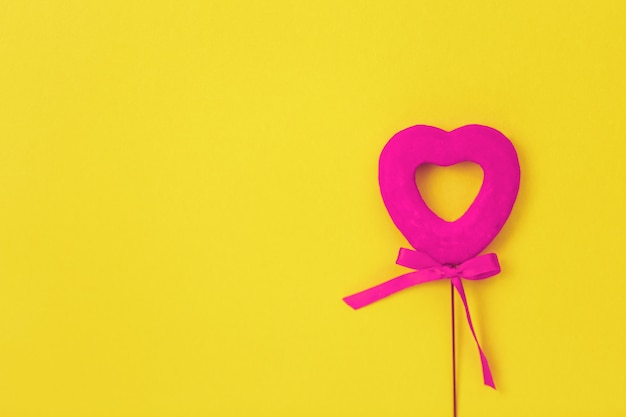 Coeur rose sur une surface jaune, arc, amour Photo Premium