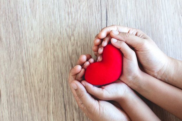 Coeur rouge dans les mains de l'enfant et parent mains sur fond de table en bois avec amour et harmonie Photo Premium