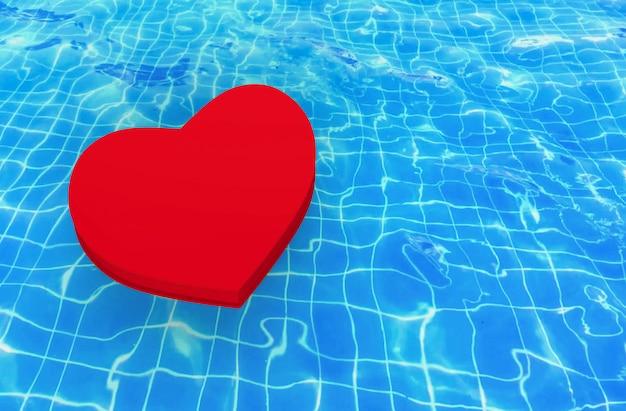 Un coeur rouge flottant sur fond de surface de piscine agitant. Photo Premium