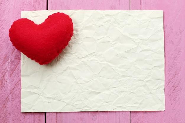 Coeur rouge placé sur une note de papier vide pour la saisie de texte ou un message en design Photo Premium