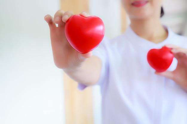 Coeur rouge tenu par la main de l'infirmière souriante Photo Premium