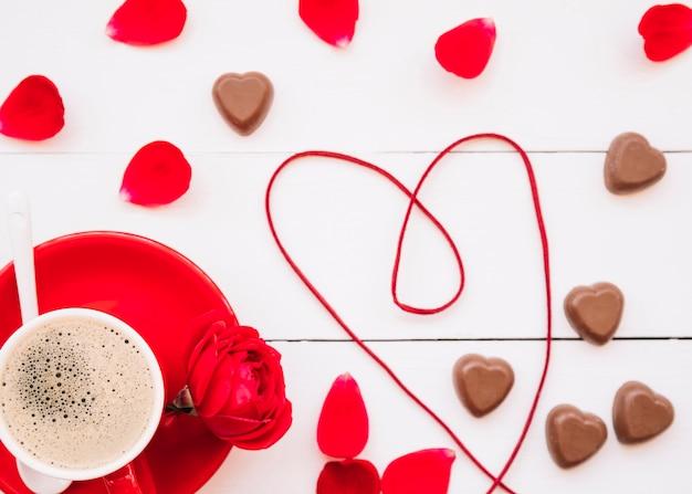 Coeur de ruban près de bonbons au chocolat, tasse sur plaque et pétales Photo gratuit