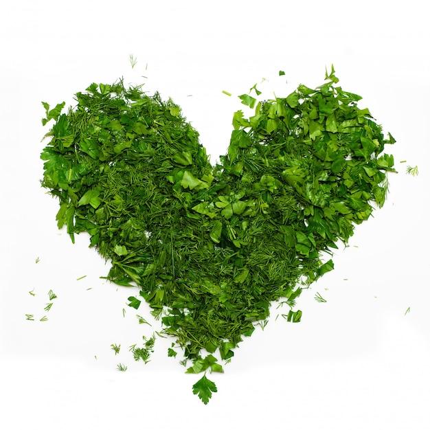 Un corazón verde de perejil picado y eneldo en blanco |  Foto premium