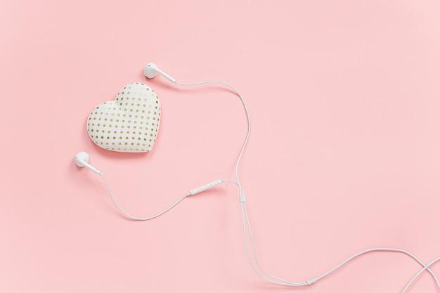 Coeur De Volume Textile Décoratif Et Casque Blanc Sur Fond Rose. écoutez Votre Cœur Ou Votre Amour De La Musique. Photo Premium