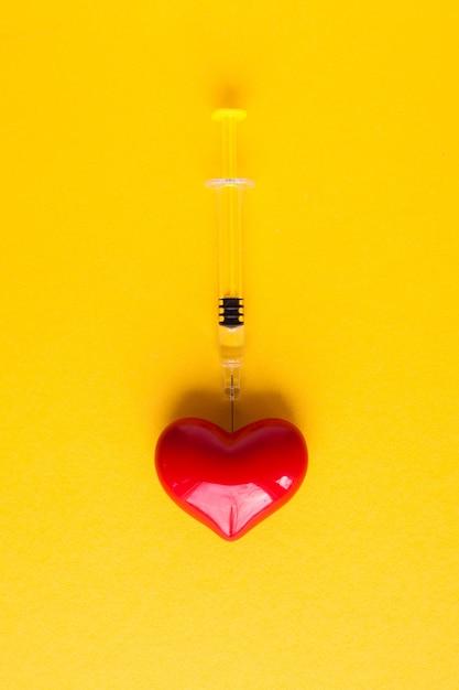 Coeur Volumétrique Avec Seringues Sur Fond Rose. Le Concept De Soutien Aux Patients Atteints De Maladie Cardiaque Photo Premium