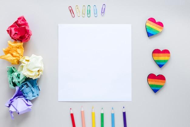 Coeurs arc-en-ciel avec papier et crayons Photo gratuit