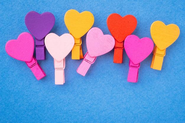 Des coeurs en bois colorés se trouvent côte à côte sur un fond bleu. Photo Premium