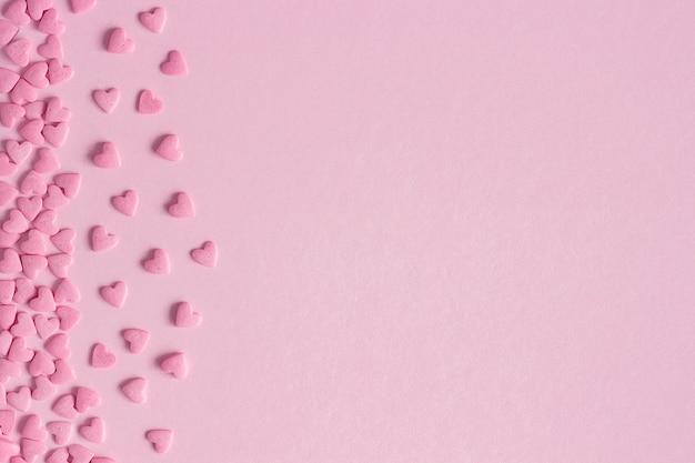 Coeurs de confiserie rose situés à gauche sur fond rose, espace copie Photo Premium
