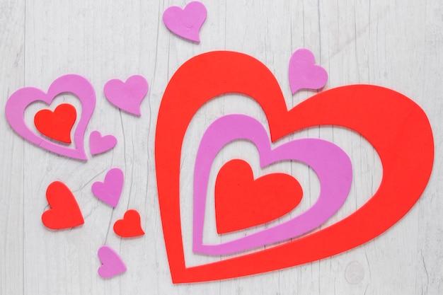 Coeurs de joli papier sur fond de bois de charpente Photo gratuit