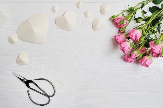 Coeurs origami blancs en papier avec roses roses et ciseaux Photo Premium