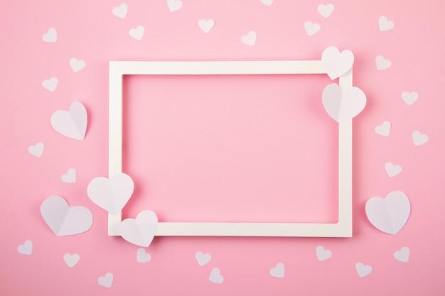 Coeurs De Papier Et Cadre Blanc Sur Le Fond Pastel Rose. Photo Premium
