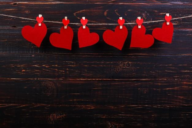 Coeurs Rouges Sur Une Corde Avec Des Pinces à Linge, Sur Un Fond En Bois Noir. Place Pour Le Texte, Espace De Copie. Photo Premium