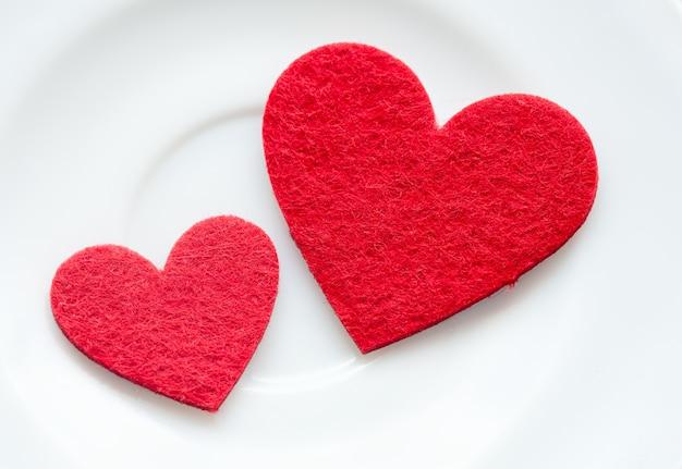 Coeurs rouges sur un gros plan de la plaque. la saint-valentin Photo Premium