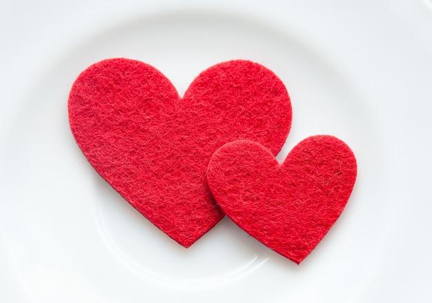 Coeurs rouges sur un gros plan de la plaque. la saint valentin Photo Premium