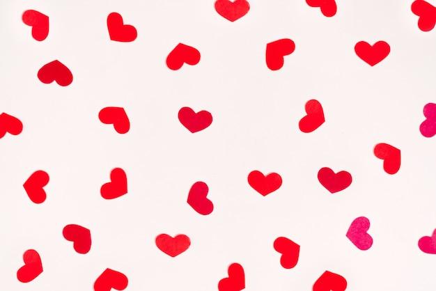 Les Coeurs Rouges Sont Dispersés Dans Un Ordre Chaotique Sur Fond Blanc. Carte De Vœux Pour La Saint Valentin Photo Premium