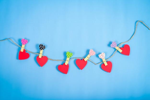 Coeurs rouges suspendus sur une corde sur fond de couleur Photo Premium