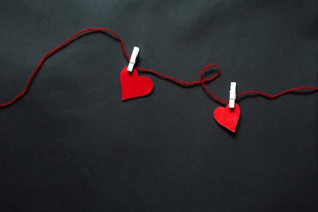 Coeurs Suspendus à Une Ficelle Sur Fond Noir. Contexte De La Saint-valentin Photo Premium