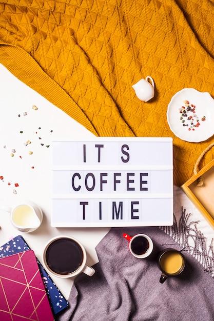 Coffee time est écrit sur une lampe décorative parmi les nombreuses tasses de café Photo Premium