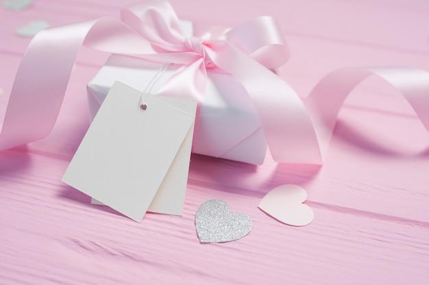 Coffret Blanc Avec Un Noeud En Satin Rose Et Ruban Sur Fond En Bois Rose. Carte De Saint Valentin Photo Premium