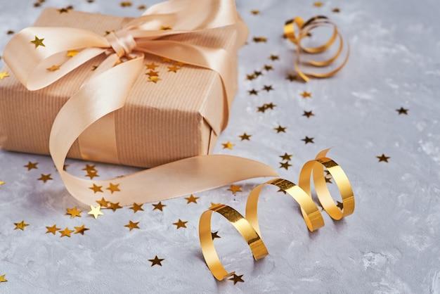 Coffret cadeau avec un arc d'or et des confettis, gros plan Photo Premium