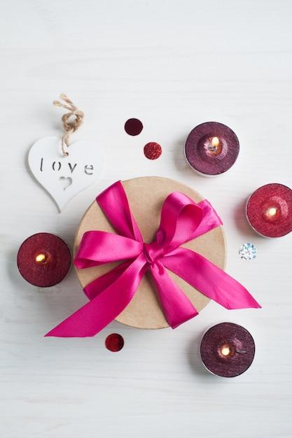 Coffret cadeau avec un arc rose et des bougies allumées Photo Premium