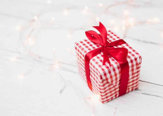 Coffret cadeau enveloppé près de guirlandes lumineuses Photo gratuit