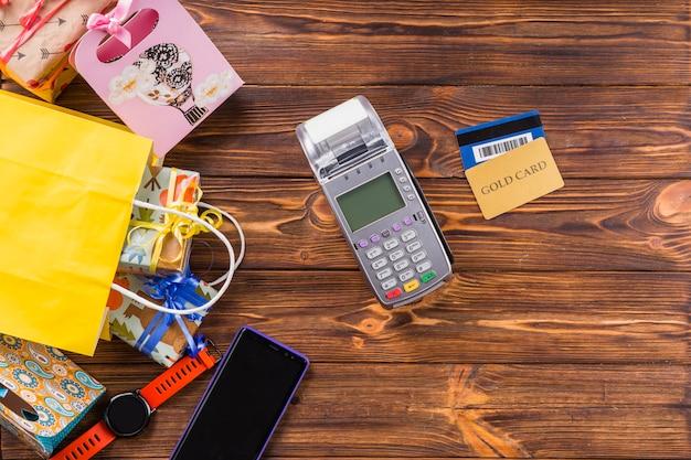 Coffret cadeau; montre-bracelet; téléphone portable; terminal de paiement et carte bancaire sur table en bois Photo gratuit