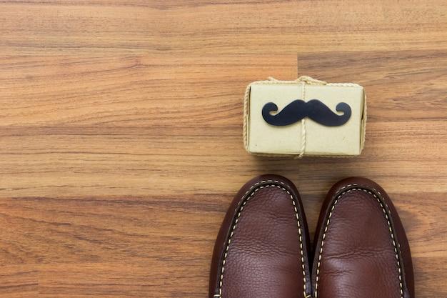 Coffret cadeau, moustache en papier, chaussures sur fond en bois avec espace de copie. joyeuse fête des pères. Photo Premium