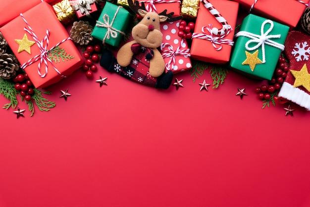Coffret cadeau de noël avec rennes et décoration sur fond rouge. Photo Premium