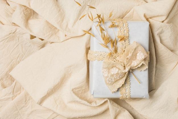 Coffret cadeau noué avec de la dentelle de créateur sur un drap froissé Photo gratuit