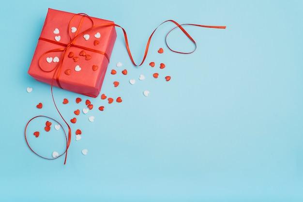 Coffret cadeau avec petits coeurs sur la table bleue Photo gratuit