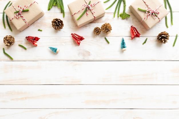 Coffret cadeau, pommes de pin, étoile rouge et cloche sur un fond blanc en bois. déco de noël Photo Premium