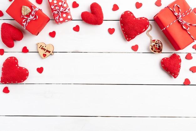 Coffret cadeau rouge, fond rouge saint valentin avec coeur rouge sur fond en bois. Photo Premium