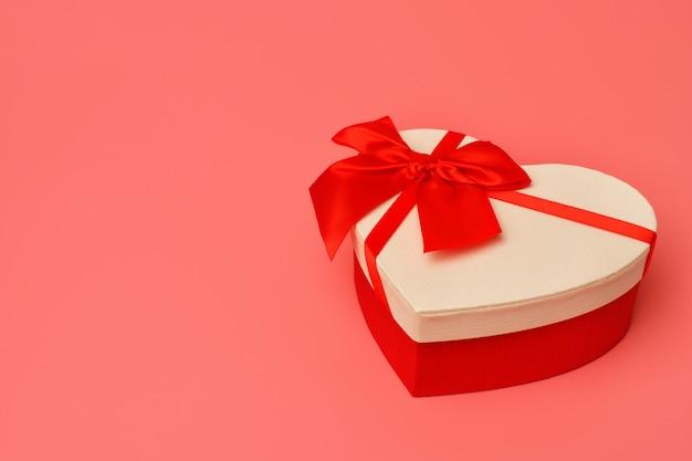 Coffret Cadeau Avec Un Ruban Rouge En Forme De Coeur Sur Fond Rose. La Saint-valentin Photo Premium