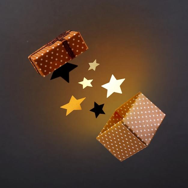 Coffret marron avec étoiles et lumière jaune sur une surface sombre anti-gravité. Photo Premium
