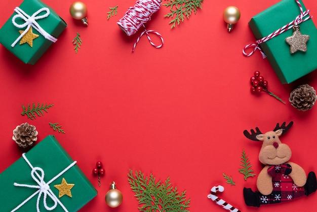 Coffret noël vert avec des branches d'épinette, des pommes de pin, des baies rouges sur fond rouge. Photo Premium
