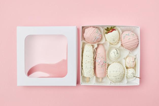 Coffret ouvert avec des fruits recouverts de chocolat blanc et rose Photo Premium