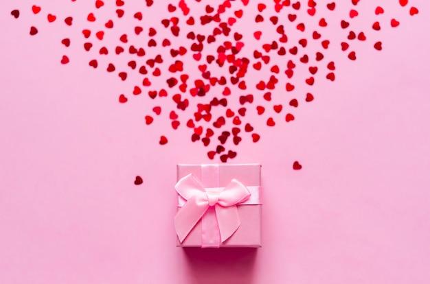 Coffret Rose Avec Des Coeurs Rouges Holographiques Sur Fond Pastel. Toile De Fond Festive. Vue De Dessus. Photo Premium