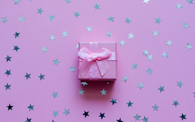 Coffret rose avec des étoiles holographiques sur fond pastel violet. toile de fond festive. vue de dessus. Photo Premium