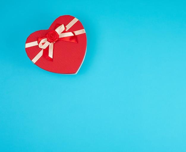 Coffret rouge en forme de coeur avec un noeud sur un fond bleu Photo Premium