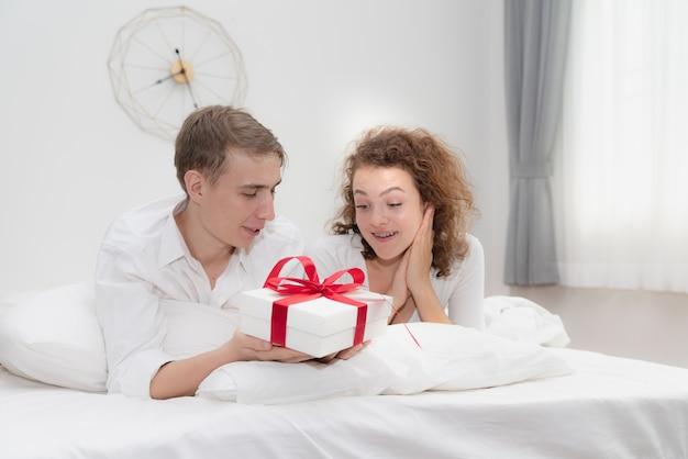Coffret surprise de jeunes couples amoureux dans la chambre Photo Premium