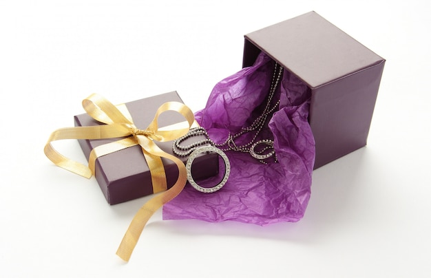 Coffret violet avec bijoux et ruban jaune sur blanc Photo Premium