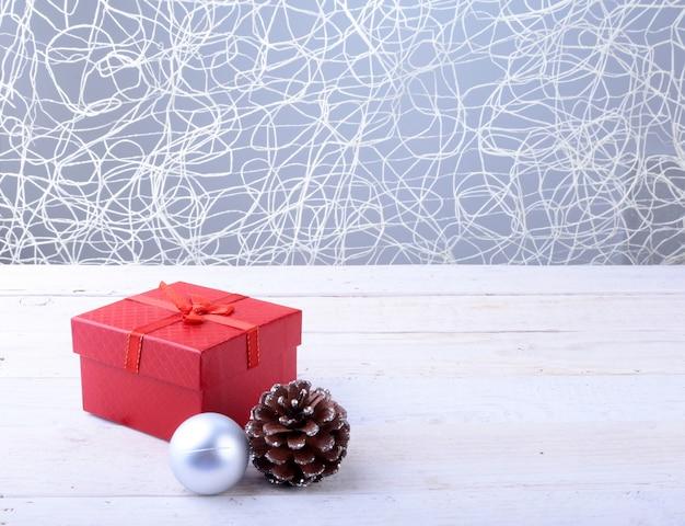 Coffrets cadeaux avec des boules de noël et arc sur fond de bois Photo Premium
