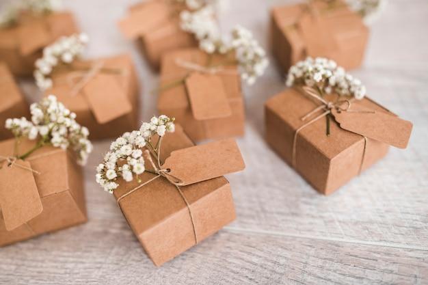 Coffrets-cadeaux en carton avec étiquette et fleurs d'haleine de bébé sur un bureau en bois Photo gratuit